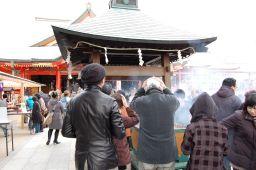 成田山不動尊の線香の煙を頭に付ける人々の写真